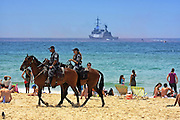 Israel, Tel Aviv, Mounted police patrol the crowded beach with an Israeli Navy missile boat in the background