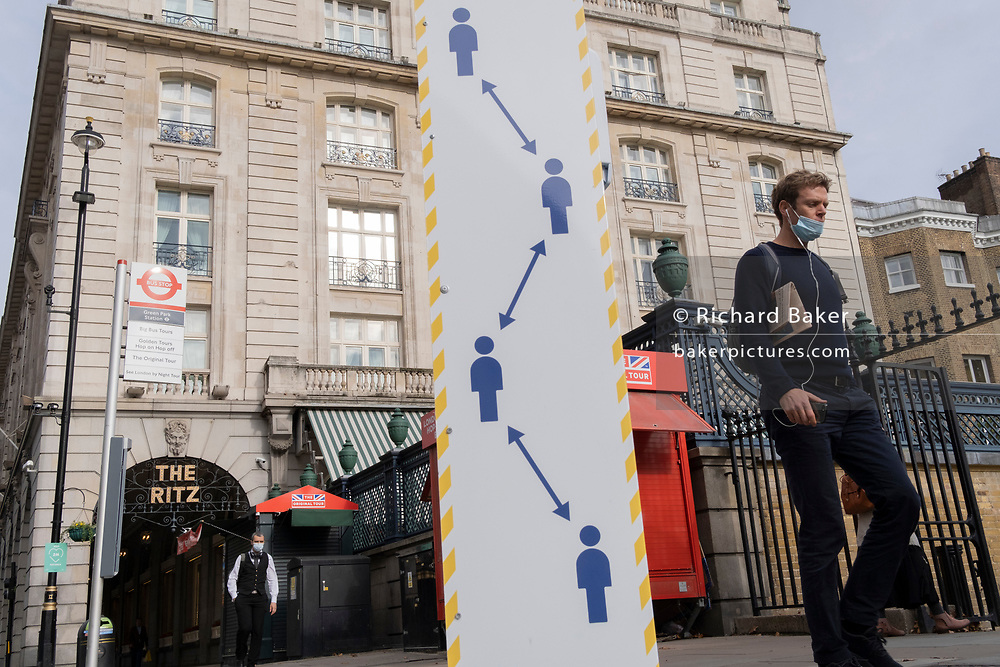 Londoners walk past a social distancing sign near the famous Ritz Hotel on Piccadilly during the second (Autumn) spike of the Coronavirus pandemic, on 5th October 2020, in London, England.
