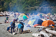 Hikers crowd onto the narrow beach campsite at Thrasher Cove, West Coast Trail, British Columbia, Canada.