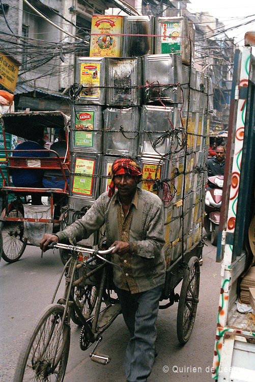 Man carries cans on bicycle, Old Delhi