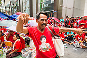 19 MAY 2013 - BANGKOK, THAILAND:   A Red Shirt dances during a Red Shirt rally in Ratchaprasong Intersection honoring Red Shirts killed by the Thai army in 2010. More than 85 people, most of them civilians, were killed during the Thai army crackdown against the Red Shirt protesters in April and May 2010. The Red Shirts were protesting against the government of Abhisit Vejjajiva, a member of the opposition who became Prime Minister after Thai courts ruled the Red Shirt supported government was unconstitutional. The protests rocked Bangkok from March 2010 until May 19, 2010 when Thai troops swept through the protest areas arresting hundreds.    PHOTO BY JACK KURTZ