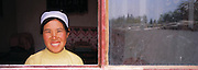 woman looking thru the window of her house at Guancai  Village. Ningxia Province, China.