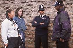 Community police officer standing in street talking to group of teenagers,