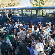 Refugees and immigrants waiting to board to the Coast Guard's bus that will take them from Molyvos to one of the camps in Mytiline