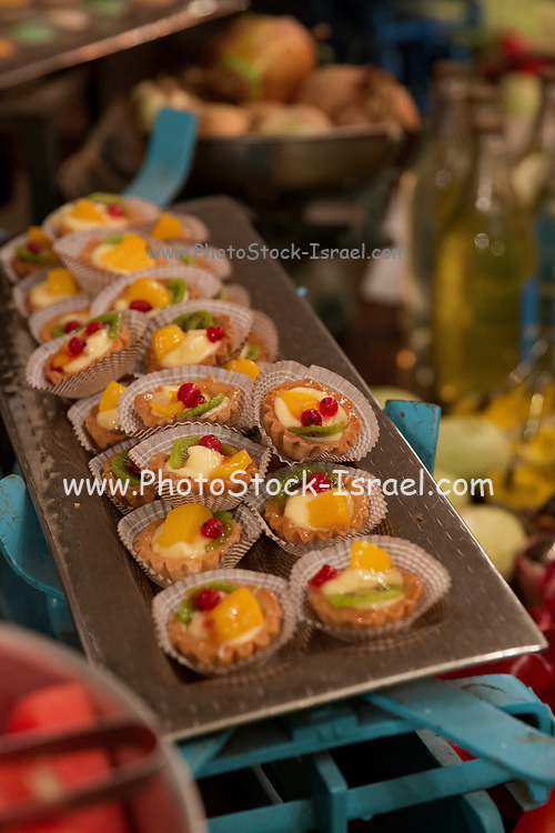 A dessert plate of sweet cream tartelettes (small tarts with various sweet fillings)