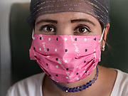 A woman wears a mask to protect herself from the dust and sand. Life inside the train - mostly Muslim Uighur people  ride this train.