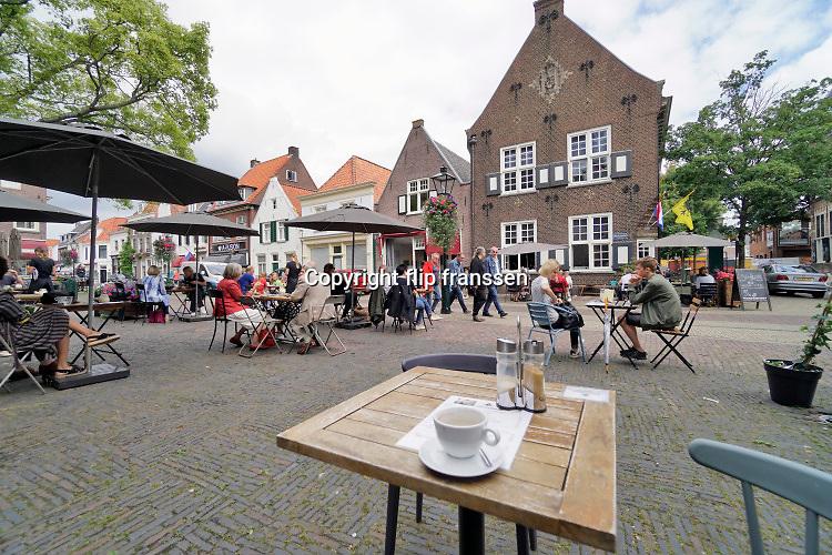 Nederland, Naarden, 24-7-2020  Een terras in het centrum van dit vestiginsstadje en toeristische hotspot . Het terrasje is coronaproof, dus tafeltjes anderhalve meter van elkaar .Foto: ANP/ Hollandse Hoogte/ Flip Franssen