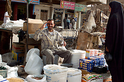 One Iraq man sits at his market stall  in front of a row of run down looking shops and salutes for the camera as an Iraqi civilian woman looks at the goods on his stall  in a market area of Basra in March 2005