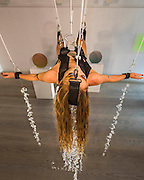 """Her head is also held in place by a strap and a wire - Performance Artist Millie Brown performs """"Rainbow Body""""- a site specific performance installation, where she suspends her body surrounded by crystal prisms, from the ceiling of the gallery on Dover Street for the duration of Frieze one of the busiest weeks in the captial's art scene. Contemporary art gallery Gazelli Art House supports and presents a wide range of international artists."""