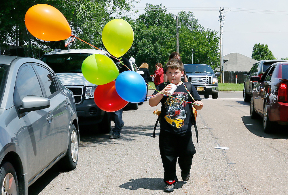 Christian Joyner, 8, a student at the tornado-destroyed Plaza Towers elementary school walks down the street after being dismissed on the last day of school in Oklahoma City, May 23, 2013. Christian's grandmother picked him up from the school just prior to the storm hitting. Seven children died in the school with the first being laid to rest today. REUTERS/Rick Wilking (UNITED STATES)