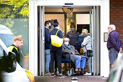 """© Licensed to London News Pictures . 10/08/2021. Wigan , UK . People stood waiting at the entrance to Royal Albert Edward Infirmary A&E in Wigan . Yesterday and today (9th and 10th August 2021) the hospital has published advice for people to stay away unless facing an emergency , as officials describe services as being """"very busy"""" . Photo credit : Joel Goodman/LNP"""