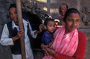 A Nepalese family with young boy visit a shrine under renovation.