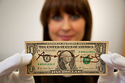 London, UK. Friday 23rd November 2012. Christies auction house showcasing memorabilia from every decade of the past century of popular culture from the industries of film and music. Christie's Specialist Caitlin Graham shows a one dollar bill signed by Andy Warhol.
