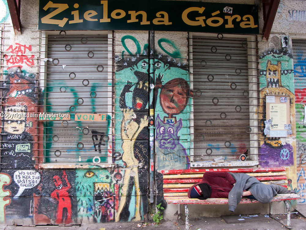 Man sleeping rough outside graffiti covered squat apartment building in Friedrichshain Berlin Germany