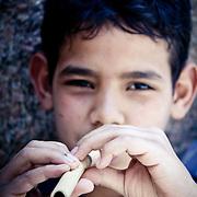 A small boy plays a home-made flute. Near Cairo, Egypt.