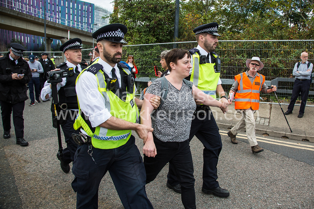 London, UK. 7 September, 2019. Metropolitan Police officers arrest an activist after the road was blocked in front of a truck attempting to deliver to ExCel London during the sixth day of Stop The Arms Fair protests against DSEI, the world's largest arms fair. The sixth day of protests was billed as a Festival of Resistance and included performances, entertainment for children and workshops as well as activities intended to disrupt deliveries to ExCel London for the arms fair.