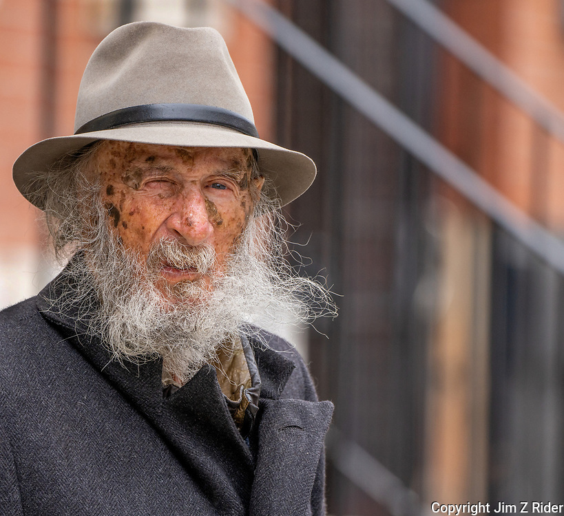 An elderly gentleman takes in the afternoon air outside of his brownstone apartment in downtown Philadelphia, PA.