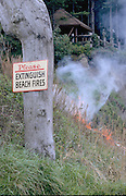 """Humorous photograph of a sign that reads """"Please EXTINGUISH BEACH FIRES"""" with a grass fire occuring right behind the sign."""