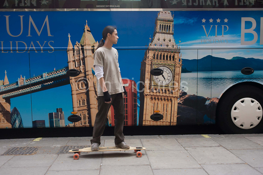A parked tour coach for Platinum Holidays features famous London landmarks as a young skateboarder rides past. On the side of the bus are the places that attract visitors to Britain's capital: Tower Bridge; Big Ben and a red telephone box.