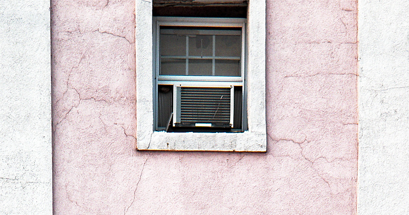 Pink and white stucco building with window air conditioner