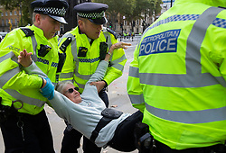 © Licensed to London News Pictures. 09/10/2019. London, UK. Police remove Extinction Rebellion protesters from a roadblock in Whitehall. Police continue to attempt to clear roads in Westminster on the third day of the protest.  Photo credit: George Cracknell Wright/LNP