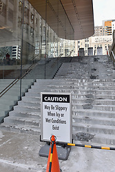 © Licensed to London News Pictures. 31/12/2017. CHICAGO, UK.  Signs warning passers by of falling ice are on display around the new flagship Apple Store, North Michigan Avenue, next to the Chicago River.  The building, designed by British architects Foster +Partners, has a roof shaped like the cover of an Apple laptop and appears to lack visible guttering.  Icicles which have formed in the current sub-zero temperatures have crashed to the ground below endangering the public and the store is currently facing criticism from locals to develop a solution.  Photo credit: Stephen Chung/LNP