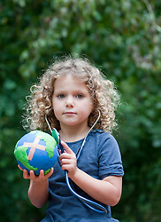 Young girl holding model of planet Earth and checking its health with a stethoscope