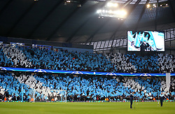 Groundsman tend to the pitch whilst Manchester City fans wave flags in the stands to show their support