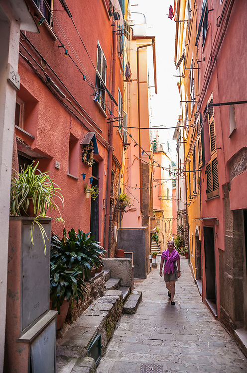 A woman walking the narrow passages of Vernazza, Italy.
