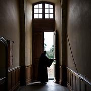 A monk stands at the priory door overlooking the formal garden of solesmes abbey. 08-01-16<br /> Un moine se tient dans l'entrée du prieuré donnant sur le jardin à la française à l'abbaye de Solesmes. 08-01-16