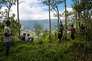 Two visitors from Europe and several local guides enjoy the view after completing a hike to the volcanic crater rim on Karkar Island in Madang Province, Papua New Guinea.
