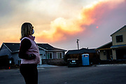 Liz Neves along Keoke Court in the Coffey Park neighborhood as smoke from the Kincade Fire fills the air on Sunday, Oct. 27, 2019, in Santa Rosa, Calif. Neves lives in her rebuilt home along Keoke Court at Mocha Lane in the Coffey Park neighborhood, where there's an evacuation warning in place. Neves, her husband and her neighbor take shifts sleeping to make sure someone is awake if an evacuation is ordered. She's been living in the neighborhood for more than 30 years. The Coffey Park neighborhood continues to rebuild after it was destroyed in the Tubbs Fire of October 2017.