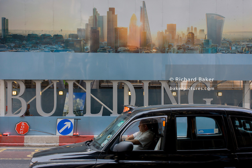 A black cab passes a large construction hoarding in the City of London, the  Square Mile, the capital's historic financial district.