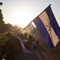 A migrant carries a Honduran flag on the road to Pijijiiapan, Chiapas