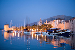 Europe, Croatia, Dalmatia, Trogir, a UNESCO World Heritage site.  Boats, historic stone buildings, Kamerlengo Castle, and the Adriatic Sea at dusk.