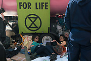 Climate protesters loacked on to the boat, being removed by Police at Oxford Circus. In an operation that took several hours, Police removed the pink boat named Berta Caceres after the Hondruan nun who was murdered for being an environmental activist, that was the centrepiece of Extinction Rebellions site. It involved people who were locked on being removed. Several roads were blocked across four sites in central London, by the Extinction Rebellion climate change protests, April 2019.
