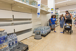 © Licensed to London News Pictures.  22/07/2021. London, UK. A shopper walks past empty shelves in Tesco, Hackney, east London. Supermarkets have warned they could start running out of food in 48 hours. Many stores had to close due to a lack of workers having to self-isolate.  Photo credit: Marcin Nowak/LNP