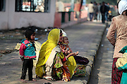 A mother and her two children begs to passengers on their way to board the train in Jaipur. Children, some who have run away from their families, find themselves living homeless on the train tracks waititng for the next train to arrive at the train station in Jaipur, India.  Once the train arrives they raid the train looking for plastic bottles that they can then sell.  Most will make about $1.50/day but spend most of it on glue which they are most addicted to.