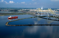 A bright red oil tanker leaving the Port of Houston near the Fred Hartman Bridge.