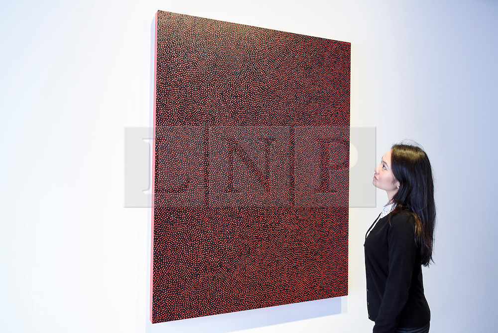 """© Licensed to London News Pictures. 17/02/2017. London, UK.   A staff member views """"Infinity Nets"""" by Yayoi Kusama, at a preview of """"Traumata: Bourgeois/Kusama"""".  The joint exhibition is dedicated to the work of Louise Bourgeois and Yayoi Kusama, and takes place at Sotheby's S/2 Gallery 23 February to 13 April. Photo credit : Stephen Chung/LNP"""