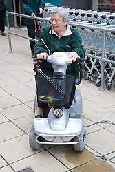 Older woman leaving shops riding an electric mobility scooter down the road,