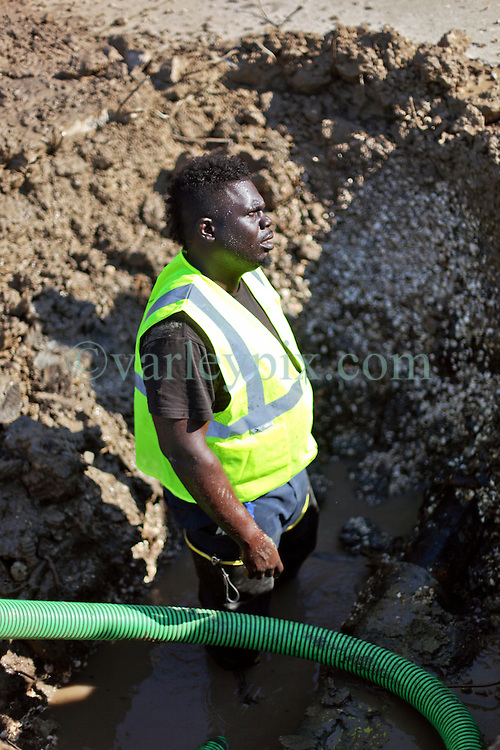 26 August 2015. New Orleans, Louisiana. <br /> Hurricane Katrina revisited. <br /> Rebuilding the Lower 9th Ward a decade later. <br /> A contractor working with the New Orleans Sewerage and Water Board get to work fixing a substantial leak below ground. Signs of a rebirth of the community following the devastation of hurricane Katrina a decade earlier.<br /> Photo credit©; Charlie Varley/varleypix.com.