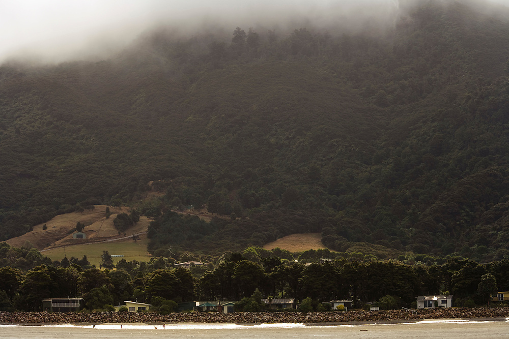 A line of beachside batches at Pakawau Beach on a muddy misty day at low tide
