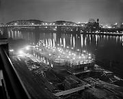 "Ackroyd 05924-04. ""Balfour - Guthrie."" night photo of grain elevator construction looking across Willamette river, Broadway bridge in background. March 14, 1955. 4x5"