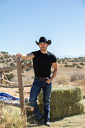 rugged cowboy opening a gate on a ranch rugged cowboy with blue eyes on a ranch