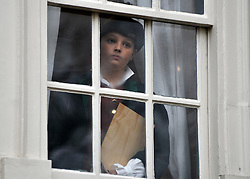 © Licensed to London News Pictures. 07/11/2011. London, UK. Peter aged 10, from The William Hogarth Primary School, looks out of a restored window, wearing clothes similar to what Hogarth would have worn in the 18th Century in garden of the house. The restoration project at Hogarth's House, built in 1750, in Chiswick, West London is completed today 7th November 2011. The house, once Hogarth's residence holds a collection of the artist's 18th century prints and engraving plates. The house suffered damage from a major fire during the restoration. Photo credit : Stephen Simpson/LNP