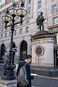In the week that many more Londoners returned to their office workplaces after the Covid pandemic, a businessman reads paperwork beneath the statue of engineer James Henry Greathead, in the City of London, the capitals financial district, on 8th September 2021, in London, England. Civil engineer James Henry Greathead 1844 -1896, is renowned for his work on the London Underground.