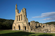 Byland Abbey, North Yorkshire, England, UK. Byland Abbey is a ruined abbey and a small village in the Ryedale district of North Yorkshire, England, in the North York Moors National Park. Impressive remains can still be seen, in the care of English Heritage, including the lower half of a huge rose window. It was founded as a Savigniac abbey in January 1135 and was absorbed by the Cistercian order in 1147. It wasn't an easy start for the community who had had to move five times before settling at New Byland, near Coxwold in 1177.