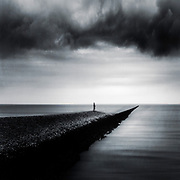 Man standing on a stone wave breaker on a stormy say - abstract photograph
