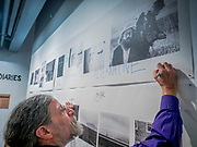 """Portland, Oregon, USA. 26 FEB, 2018. Blue Sky Gallery co-founder Christopher Rauschenberg, son of the American painter Robert Rauschenberg, defaces a Robert Frank image of the poet Alan Ginsberg  at Blue Sky Gallery in Portland, Oregon, USA. The work was destroyed in a """"Destruction Dance"""" performance defacing the photographs with ink and mutilation with scissors, knives and even ice skates  at the end of it's run. The destruction was Frank's protest regarding today's greed in the global art market."""